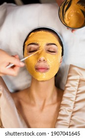 Procedure for skin care. Doctor in cosmetology office applies an yellow gold alginate mask to the face of young pretty woman.