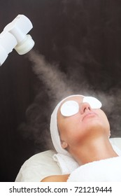 The procedure of steaming the skin of the face of a young woman before cleaning the skin, in a cosmetology salon.