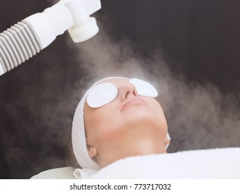 The procedure of steaming the skin of the face of a young woman before cleaning the skin in a cosmetology salon.