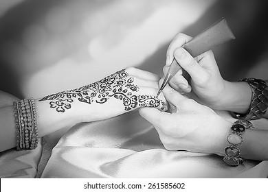 Process of applying Mehndi on female hand, close up