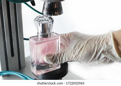 The process of aroma body perfume glass bottle is closed tight by the body perfume sealer machine which use air power from the air pump in the factory of body perfume company with white background
