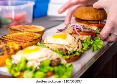 The process of assembling the morning burger with an appetizing meatball fried egg and vegetables