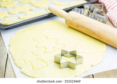 The process of baking cookies at home, closeup on cookie cutter on dough and rolling pin on a wooden board