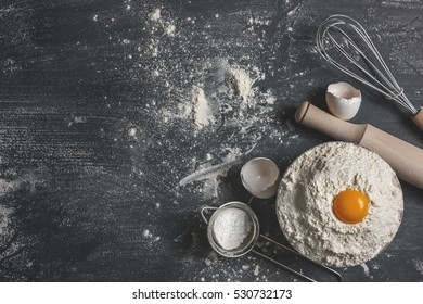 The process of baking, cooking. Flour sprinkled on gray table, rolling pin, whisk, egg shells sieve and spoon filled with flour. Pile the flour into a bowl with the egg yolk. Top view, space for text