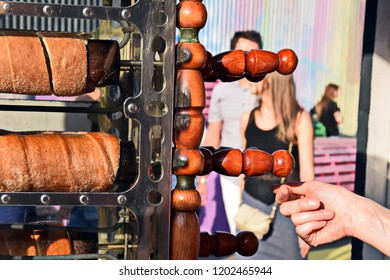 The process of baking trdelnik. Traditional Czech sweet treat Trdelnik. To prepare on a special wooden skewers over hot coals. A popular dish among tourists.