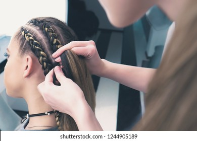 the process of braiding the master weaves braids on her head in a beauty salon close up,