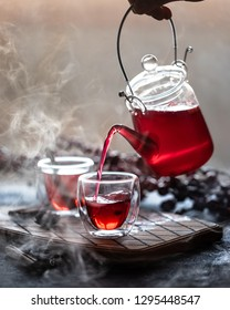 The process of brewing tea, tea ceremony, a cup of freshly brewed fruit and herbal tea. Hot tea is poured from the kettle into the cup.
