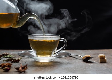 Process brewing tea,dark mood.The steam from hot tea is poured from the kettle into a kettle with tea leaves redcurrant mandarin orange lemon,rosemary, mint.,hot food and healthy meal concept