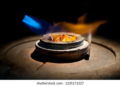 process of casting gold, melting golden metal in furnace with fire for making jewelry