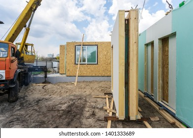 Process of construction new and modern modular house from composite sip panels. Energy efficient panel standing near new building and crane