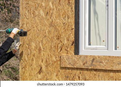 Process of construction new and modern modular house from composite sip panels. Worker man in uniform wear using electric drill working on building development industry of energy efficient property