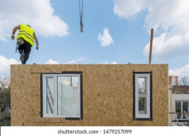 Process of construction new and modern modular house. Builder man standing on sip panel in special protective uniform wear working on building development industry of energy efficient property