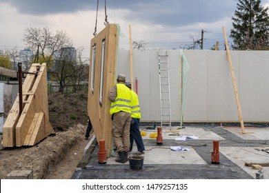 Process of construction new and modern modular house from composite sip panels. Two worker man in special protective uniform wear working on building development industry of energy efficient property