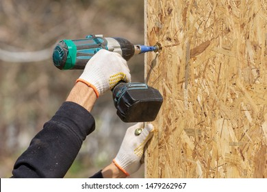Process of construction new and modern modular house from composite sip panels. Collar worker using drill and working on building development industry of energy efficient property