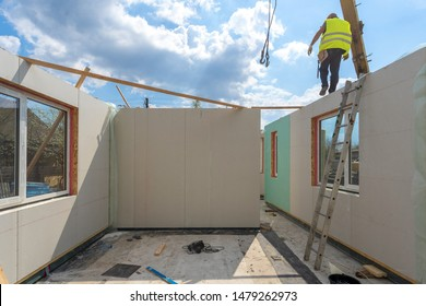 Process of construction new and modern modular house from composite sip panels. Worker man in special protective uniform wear working on building development industry of energy efficient property