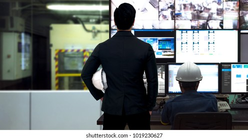 Process Control room and Industrial Automation in industry 4.0 technology trend concept. Engineer and director manager monitoring real time work automation machine process in smart factory.