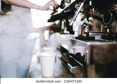 The process of cooking coffee is shown. Two glasses are standing next to a coffee machine, while barista is getting ready in a cozy coffee shop.
