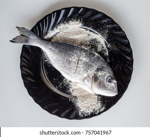 The process of cooking dorado fish. fish in flour on a black plate