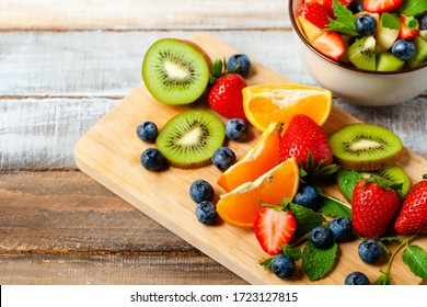Process of cooking low calories delicious dessert. Ingredients for summer fresh bowl with colorful fruit salad. Healthy natural organic food. Close up macro wooden background copy space for text