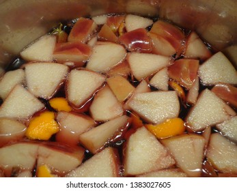 The process of cooking mulled wine with fruit pieces.