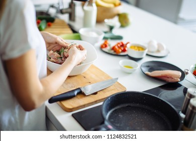 Process of cooking Raw diet kebab from fresh vegetables on skewers. woman's hand marinating chiken meat in dish on the kitchen table