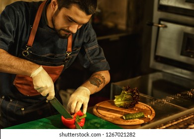 Process of cooking vegetable salad. Chef cutting paprika and other fresh vegetables using special knife. Man wearing apron and white gloves. Background of restaurant kitchen.