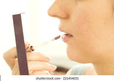 The process of cosmetic paint woman's lips on white background