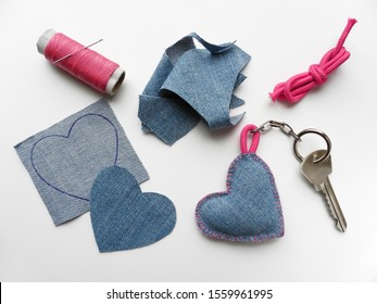 Process of creating denim heart keychain. Desktop with cut cloth, spool of thread with needle, pink cord and finished keychain with key. Handmade gift. Valentine's day concept.