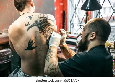 the process of creating a tattoo on the back of a man. Professional tattoo.