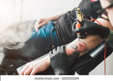 the process of creating a tattoo. tattoo parlor. a man doing a tattoo on a guy arm.