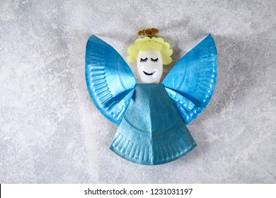 The process of creating your own Christmas angel from a disposable cardboard plate, a plastic spoon and paper. Christmas decor. Handmade, hobby, DIY