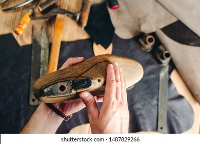 Process of creation custom made shoes. Hands of cobbler dealing with cobbler tool, close up. Workplace of shoe designer. Small business, modelling new shoes.