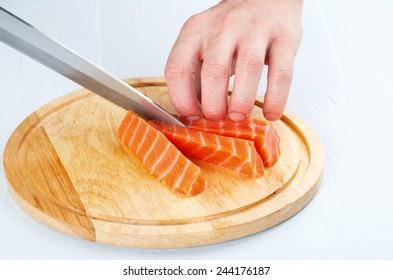 the process of cutting salmon on a cutting board closeup