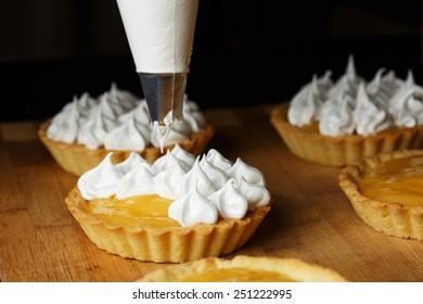 A process of decorating lemon tartlets with meringue icing