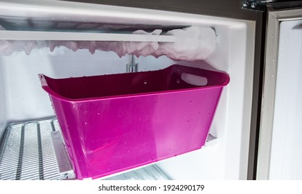 Process of defrosting ice in a home freezer. Collecting water in a plastic basin.