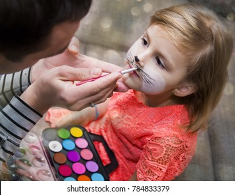 Process drawing a face painting on a child's face