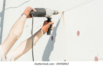 The process of drilling holes in the white polyfoam of using electric drills