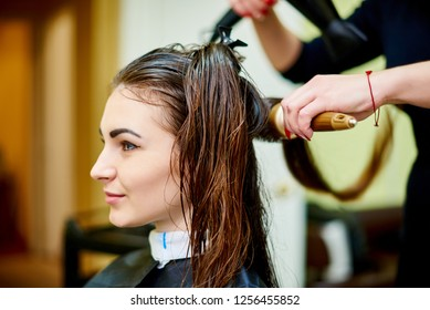 The process of drying the hair of a young beautiful girl