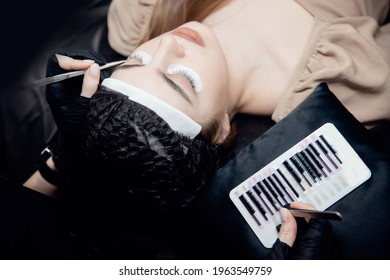 Process Eyelash extension procedure top view. Master tweezers fake 2d lashes beautiful female eyes.