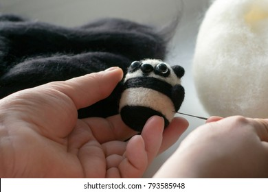 Process of felting a little toy panda from a white and black wool