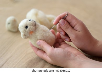 Process of felting a toy from a wool on a wooden background
