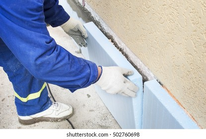 The process of gluing blue  polystyrene to wall outdoors