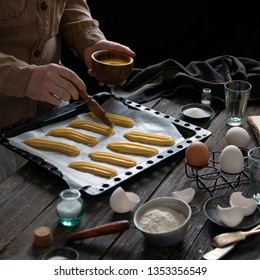 Process of greasing unbaked eclairs with eggs on baking pan by women on rustic dark table with strainer with flour, salt, sugar, spoons, eggs, glasses. Cooking french dessert eclairs. Dark food photo.