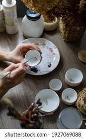 The process of hand-painting a ceramic hand-made bowl. Emphasis on the beautiful female hands of the artist.