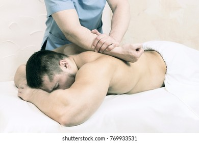 The process of health-improving sports massage is done by a man in a medical clinic