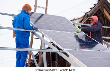 Process of installation of the solar battery by two workers in winter. Outdoors