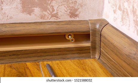process installing baseboard,mounting and assembly plinth closeup.