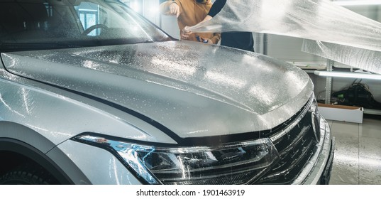 Process of installing of Paint Protection Film or PPF on new car in professional auto Detailing Center. Thin polyurethane film or polymer as protective skin from scratches and rock chips