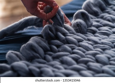 The process of knitting blankets made of Merino. blanket made of natural sheep wool. hand yarn close-up. home produces handmade plaid. designer volumetric blanket. loop weaving knits with bare hands