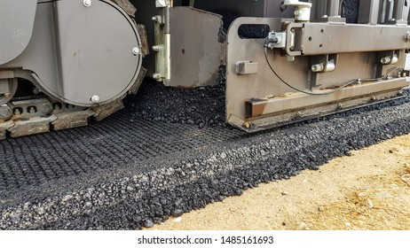 the process of laying a pavement of several layers of asphalt on a sand base. Heavy dimensional machinery rolls asphalt.